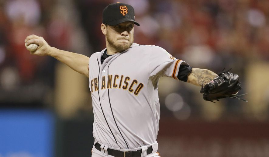 FILE - In this Oct. 12, 2014, file photo, San Francisco Giants starting pitcher Jake Peavy throws during the second inning in Game 2 of the National League baseball championship series against the St. Louis Cardinals in St. Louis.  A person familiar with the negotiations says pitcher Jake Peavy has agreed to a $24 million, two-year contract to stay with the World Series champion San Francisco Giants. The person spoke on condition of anonymity to The Associated Press on Friday, Dec. 19, 2014, because the agreement had not yet been announced. (AP Photo/Jeff Roberson, File)