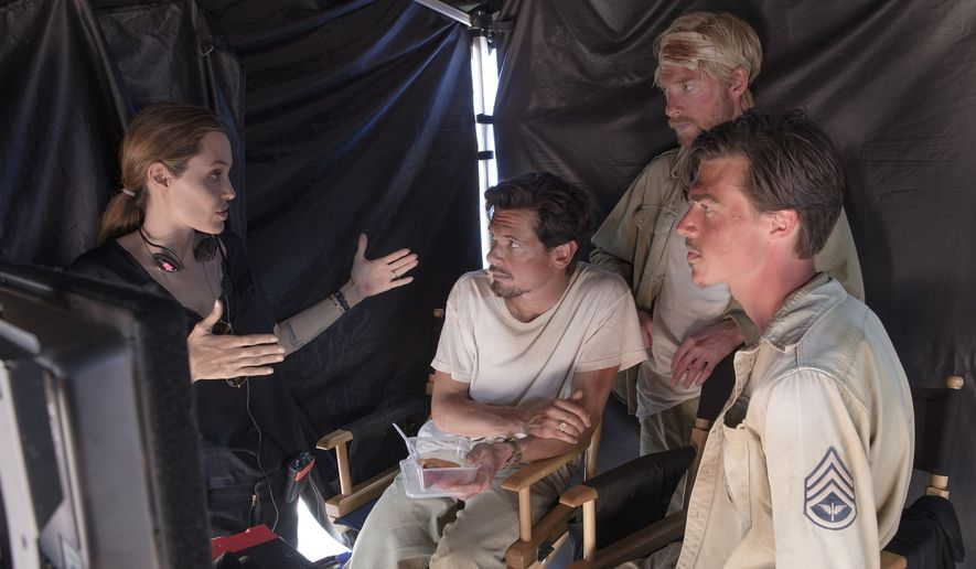 "In this image released by Universal Pictures, director Angelina Jolie, from left, speaks with actors Jack O'Connell, Domhnall Gleeson and Finn Witrock on the set of ""Unbroken."" (AP Photo/Universal Pictures, David James)"