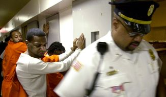 FILE PHOTO - Inmates Donnell Howard (foreground) and John Lawrence (background) wait handcuffed outside their cells while corrections officers search for contraband and weapons during a suprise search at the Washington DC Central Detention facility in Washington DC on Thursday, May 30, 2002.  The unannounced searches take place at least once a year and are planned so as to not allow inmates time to dispose of the weapons. Inmates are required to have paperwork for items such as authorized medication.  ( Gerald Herbert / The Washington Times )