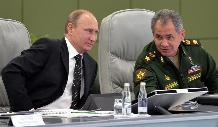Russian President Vladimir Putin, left with Defense Minister Sergei Shoigu,  heads a meeting with senior military officials in the Defense Ministry's control room in Moscow, Russia on Friday, Dec. 19, 2014. (AP Photo/RIA Novosti, Alexei Druzhinin, Presidential Press Service)