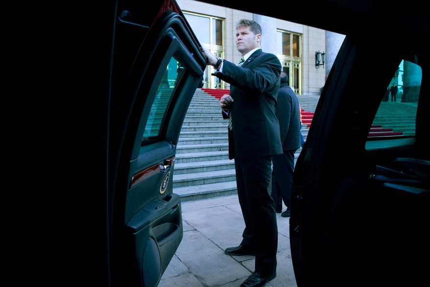 A U.S. Secret Service agent waits by the spare limousine before President Barack Obama's motorcade departs for a tour of the Forbidden City in Beijing, China, Nov. 17, 2009. (Official White House Photo by Pete Souza)