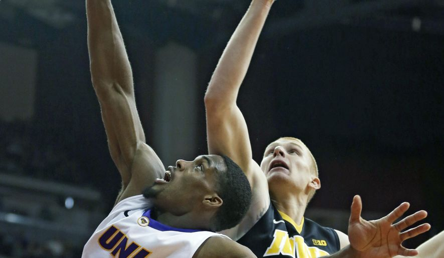 Northern Iowa forward Marvin Singleton, left, fights for a rebound with Iowa forward Aaron White during the first half of an NCAA college basketball game, Saturday, Dec. 20, 2014, in Des Moines, Iowa. (AP Photo/Charlie Neibergall)