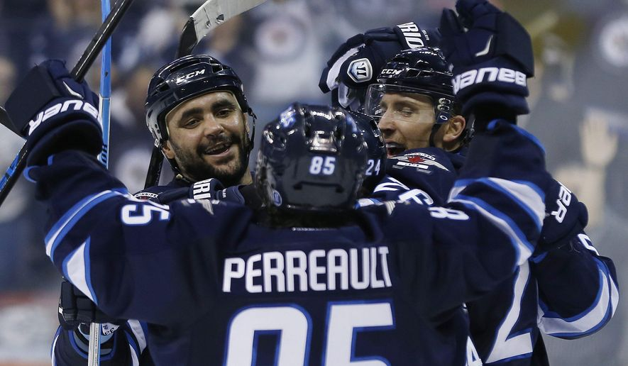 Winnipeg Jets' Dustin Byfuglien, left, Mathieu Perreault (85), Grant Clitsome (24) and Blake Wheeler (26) celebrate Byfuglien's goal against the Boston Bruins during the second period of an NHL hockey game Friday, Dec. 19, 2014, in Winnipeg, Manitoba. (AP Photo/The Canadian Press, John Woods)