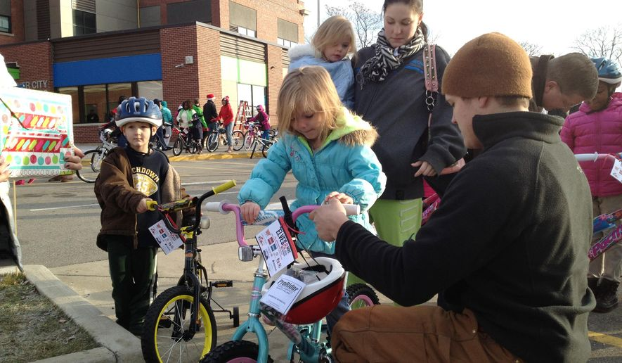Shadon Harbison, 5, gets her new bike checked out by a volunteer at the West Michigan Elves & More bike giveaway in Grand Rapids, Mich., Saturday, Dec. 20, 2014. More than 300 volunteers turned out Saturday to match kids with new wheels and a helmet. It was the 10th annual delivery, but the location always is a secret until the day of delivery. (AP Photo/The Grand Rapids Press, John Tunison)