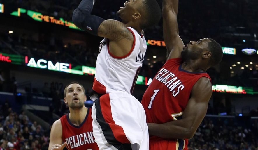 Portland Trail Blazers guard Damian Lillard, center, drives to the basket around New Orleans Pelicans forward Tyreke Evans (1) in the first half of an NBA basketball game Saturday, Dec. 20, 2014, in New Orleans, La. (AP Photo/Butch Dill)
