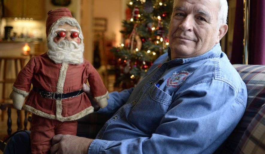ADVANCE FOR USE SATURDAY, DEC. 20 - In this photo taken on Dec. 12, 2014, Michael Fields holds his vintage Christmas doll Blinkey in the family room of his home in Spotsylvania, Va. The Doll, circa 1947, has been in his family since he was a child and adorned the window of his father's bakery in Staunton, Va., where Fields grew up. Fields and his wife uncovered the doll after moving into their home some 11 years ago, and has now reincorporated the family heirloom into the house Christmas display. (AP Photo/The Free Lance-Star, Reza A. Marvashti)