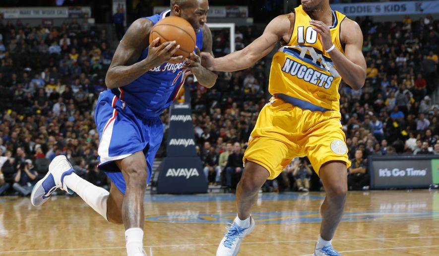 Los Angeles Clippers guard Jamal Crawford, left, drives to shoot past Denver Nuggets guard Arron Afflalo in the first quarter of an NBA basketball game Friday, Dec. 19, 2014, in Denver. (AP Photo/David Zalubowski)