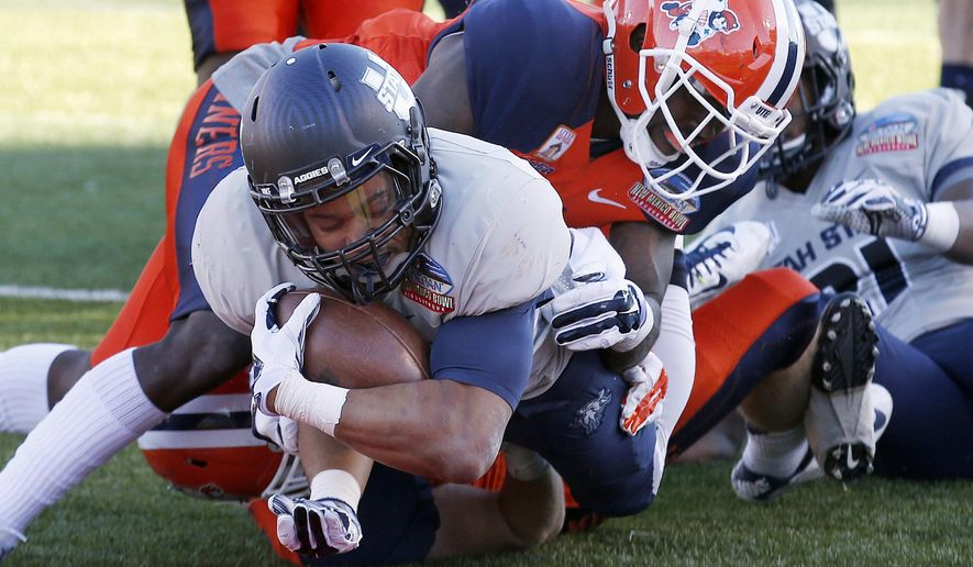 Utah State's Joe Hill, left, dives for the end zone for a touchdown as UTEP's Adrian James, right, is unable to make the tackle in time during the second half of the New Mexico Bowl NCAA college football game Saturday, Dec. 20, 2014, in Albuquerque, N.M. Utah State won 21-6. (AP Photo/Ross D. Franklin)