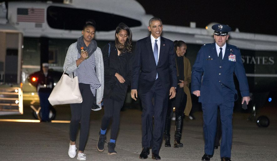 The first family, Sasha Obama, left, Malia Obama, President Barack Obama, and first lady Michelle Obama, in second row, walk to board Air Force One from Andrews Air Force Base, Md., Friday, Dec. 19, 2014, en route to their family vacation in Hawaii. (AP Photo/Jacquelyn Martin)