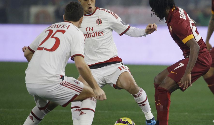 Roma's Gervinho, right, and AC Milan's Keisuke Honda fight for the ball during their Serie A soccer match between Roma and AC Milan at Rome's Olympic stadium, Saturday, Dec. 20, 2014. (AP Photo/Gregorio Borgia)