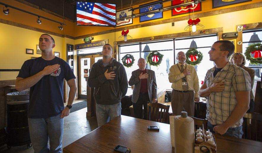 ADVANCE FOR THE WEEKEND OF DEC. 20-21 AND THEREAFTER - In a Dec. 8, 2014 photo, At Noon the sports programs on the TV's at Mission BBQ are replaced with the American flag as Nathan Diffley, Brad Pugh, Bill Wright of Norfolk, an Army veteran and his son, Matt Wright of North Carolina and Matt Hodge all stand covering their hearts as the national anthem is played at the restaurant on South Independence Blvd. Diffley, Pugh and Hodge are all Virginia Beach firefighters (AP Photo/The Virginian-Pilot, Bill Tiernan)  MAGS OUT