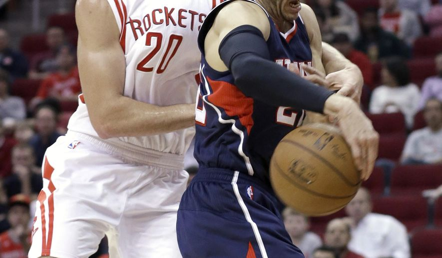 Houston Rockets' Donatas Motiejunas (20) and Atlanta Hawks' Kyle Korver fight for a loose ball in the first half of an NBA basketball game Saturday, Dec. 20, 2014, in Houston. (AP Photo/Pat Sullivan)