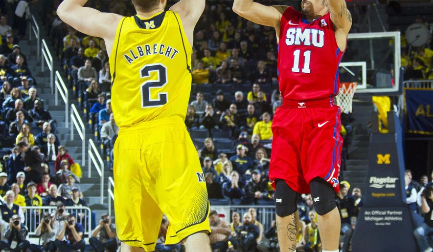 Michigan guard Spike Albrecht (2) defends a shot from Southern Methodist guard Nic Moore (11), in the first half of an NCAA college basketball game at Crisler Center in Ann Arbor, Mich., Saturday, Dec. 20, 2014. (AP Photo/Tony Ding)