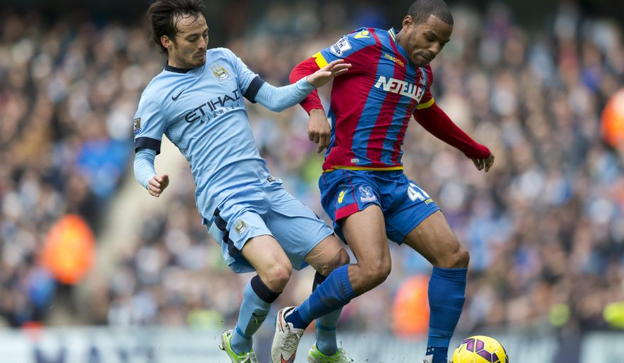 Manchester City's David Silva, left, fights for the ball against Crystal Palace's Jason Puncheon during the English Premier League soccer match between Manchester City and Crystal Palace at the Etihad Stadium, Manchester, England, Saturday Dec. 20, 2014. (AP Photo/Jon Super)