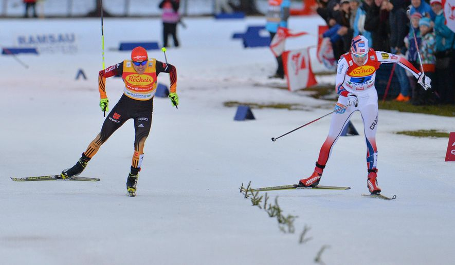 Germany's Fabian Riessle, left, and Norway's Joergen Graabak arrive in the finish area during the Nordic Combined World Cup team competition in Ramsau, Austria, on Saturday, Dec. 20, 2014. Team Norway won the competition ahead of Germany. (AP Photo/Kerstin Joensson)