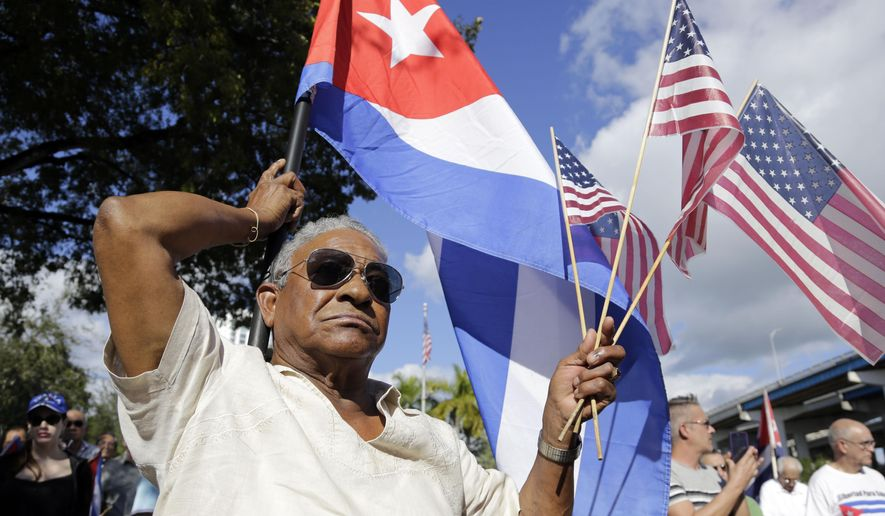 "Evilio Ordonez holds Cuban and American flags during a protest against President Barack Obama's plan to normalize relations with Cuba, Saturday, Dec, 20, 2014, in the Little Havana neighborhood of Miami. The last three members of the ""Cuban Five"" spy ring were freed this week in a sweeping deal that included the release of American contractor Alan Gross and a Cuban  who had spied for the U.S. (AP Photo/Lynne Sladky)"