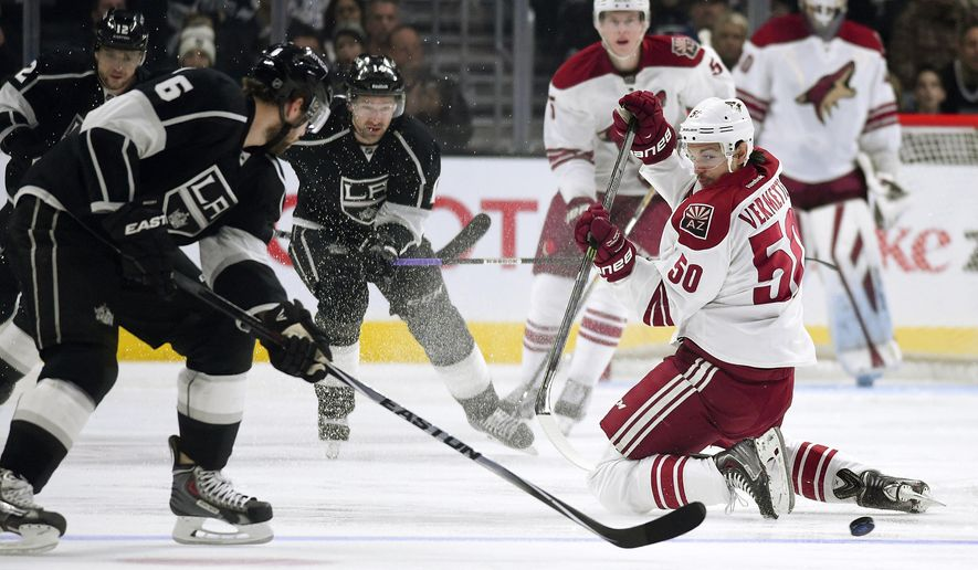 Arizona Coyotes center Antoine Vermette, right, passes the puck under pressure from Los Angeles Kings defenseman Jake Muzzin, left, during the first period of an NHL hockey game, Saturday, Dec. 20, 2014, in Los Angeles. (AP Photo/Mark J. Terrill)