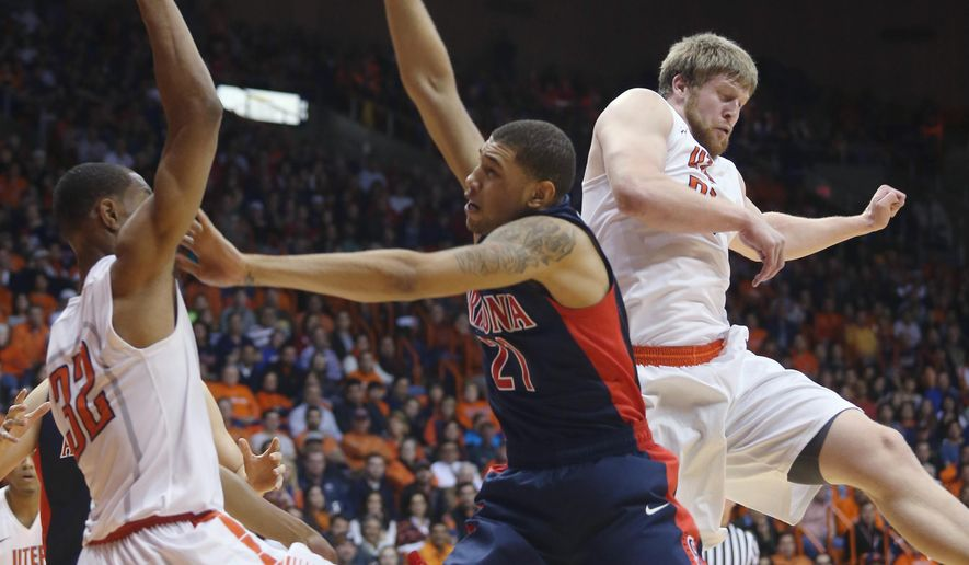 Arizona's Brandon Ashley, center, loses control of the ball as he attempts to score between UTEP defenders Vince Huner, left, and Cedrick Lang during the first half of an NCAA college basketball game Friday, Dec. 19, 2014, in El Paso, Texas. (AP Photo/Victor Calzada)