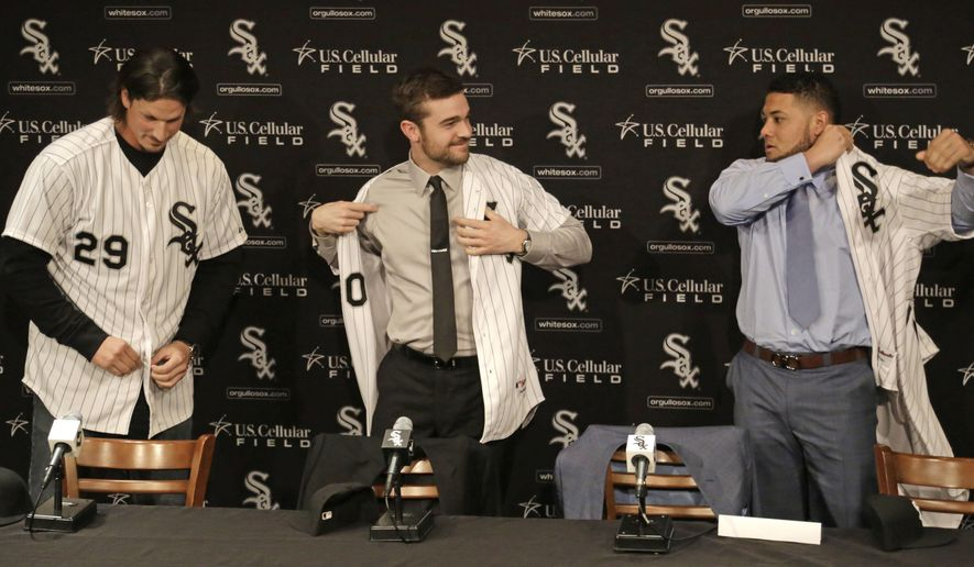 FILE - In this Dec. 16, 2014, file photo, from left to right, pitchers Jeff Samardzija and David Robertson and free-agent outfielder Melky Cabrera, right, don their baseball jerseys while being introduced as the newest Chicago White Sox at a news conference in Chicago. It is not just Sox baseball fans who are thinking big this year. So are the Cubs. North Side and South Side, there is a big baseball buzz in Chicago. (AP Photo/M. Spencer Green, File)