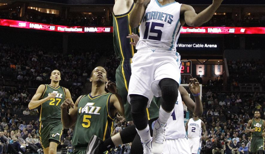 Charlotte Hornets' Kemba Walker, front, drives past Utah Jazz's Gordon Hayward, back, during the first half of an NBA basketball game in Charlotte, N.C., Saturday, Dec. 20, 2014. (AP Photo/Chuck Burton)