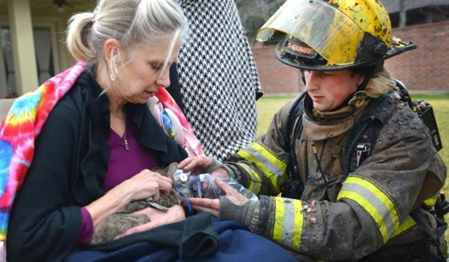 This Dec. 19, 2014 photo provided by the Fort Worth Texas Fire Department shows a firefighter providing oxygen to rescued cat from a house fire in Fort Worth, Texas.  The Fort Worth Fire Department announced Saturday, Dec. 20,  that the pet, named Stubby, survived. No one was hurt in Friday's fire, which heavily damaged a home. Authorities are trying to determine what sparked the fire.  (AP Photo/Fort Worth Texas Fire Dept.)