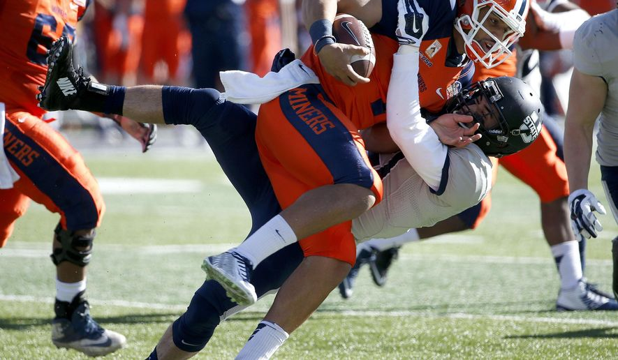 UTEP's Jameill Showers, front, is tackled by Utah State's Brian Suite during the first half of the New Mexico Bowl NCAA college football game Saturday, Dec. 20, 2014, in Albuquerque, N.M. (AP Photo/Ross D. Franklin)