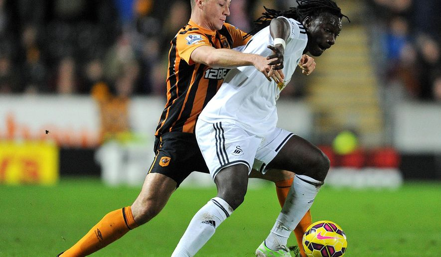 Swansea City's Bafi Gomes foreground and Hull City's James Chester vie for the ball, during the English Premier League soccer match between Hull City and Swansea City, at the KC Stadium, in Hull, England, Saturday, Dec. 20, 2014. (AP Photo/PA, Anna Gowthorpe) UNITED KINGDOM OUT NO SALES