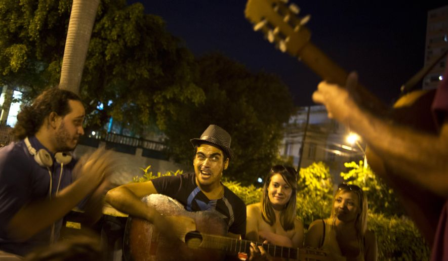 Youths sing and play music as they hang out in a park in Havana, Cuba, late Friday, Dec. 19, 2014. For a generation that grew up believing the best way to pursue their dreams was to leave the island, the announcement this week that Cuba will open relations with the U.S. is prompting many to reevaluate their futures. Also, Cuban-Americans are considering what the changes will mean for their lives, whether they are significant enough to present a once far-fetched chance for them to return. (AP Photo/Ramon Espinosa)