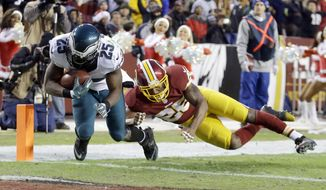 Philadelphia Eagles running back LeSean McCoy (25) carries the ball into the end zone for a touchdown under pressure from Washington Redskins cornerback Bashaud Breeland (26) during the first half of an NFL football game in Landover, Md., Saturday, Dec. 20, 2014. (AP Photo/Patrick Semansky)