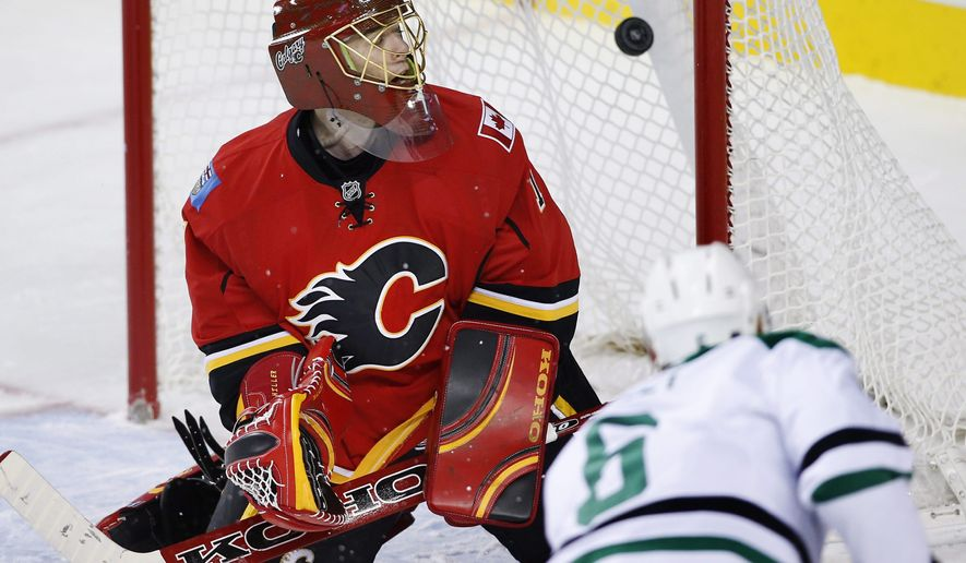 Dallas Stars' Trevor Daley, right, scores against Calgary Flames goalie Jonas Hiller, from Switzerland, during the second period of an NHL hockey game, Friday, Dec. 19, 2014 in Calgary, Alberta. (AP Photo/The Canadian Press, Larry MacDougal)