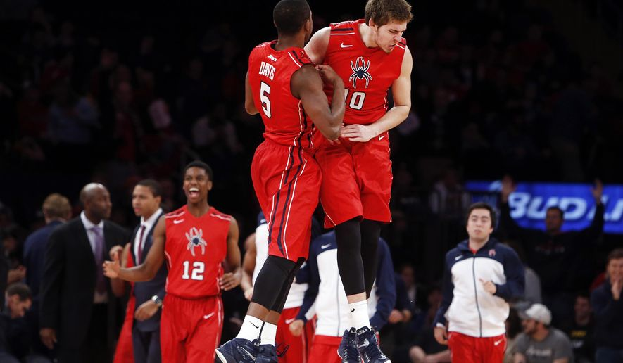 Richmond's Trey Davis (5) and T.J. Cline (10) celebrate at the end of regulation during an NCAA college basketball game Saturday, Dec. 20, 2014, in New York.  Richmond won 65-63. (AP Photo/Jason DeCrow)