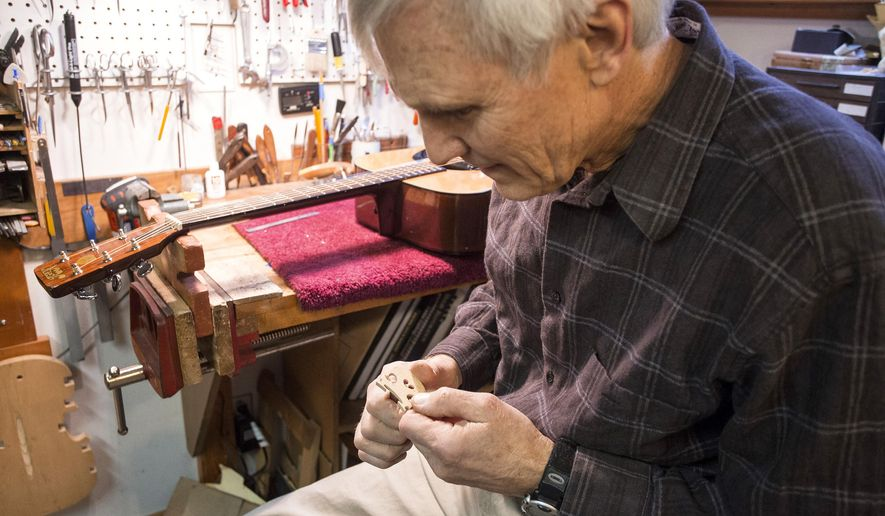 Paul Hill carves adjustments into a violin bridge using a special knife he built for the task, in the wooden instrument repair area of his basement on Friday, Nov. 28, 2014, in Moscow. (AP Photo/Moscow-Pullman Daily News, Dean Hare)