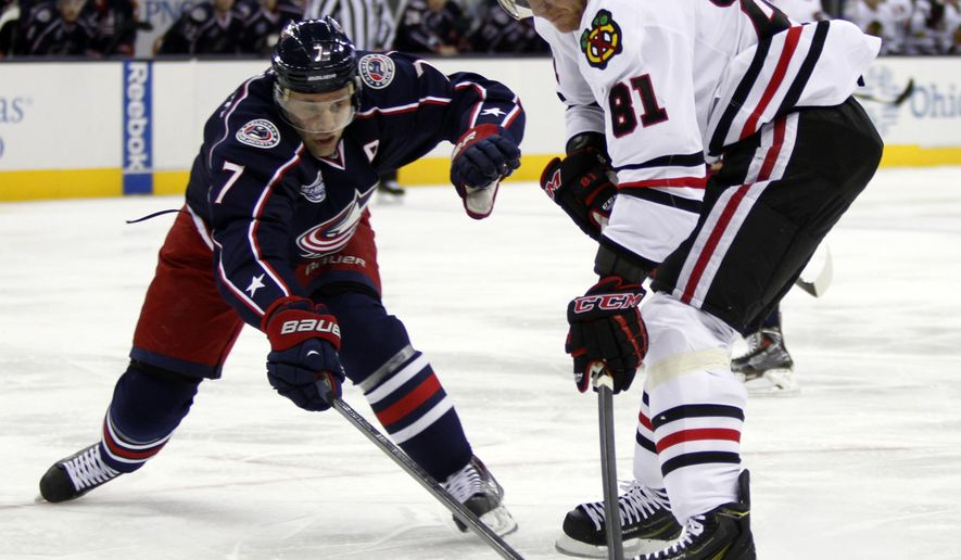 Chicago Blackhawks' Marian Hossa, right, of Slovokia, works for the puck against Columbus Blue Jackets' Jack Johnson during the first period of an NHL hockey game in Columbus, Ohio, Saturday, Dec. 20, 2014. (AP Photo/Paul Vernon)
