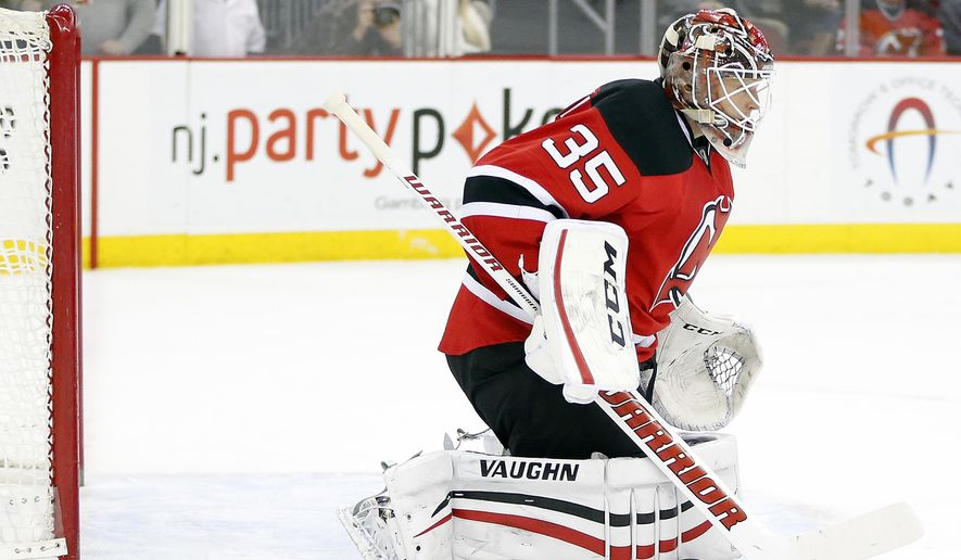 New Jersey Devils goalie Cory Schneider makes a save on a shot by the Washington Capitals during a first period of an NHL hockey game, Saturday, Dec. 20, 2014, in Newark, N.J. (AP Photo/Julio Cortez)