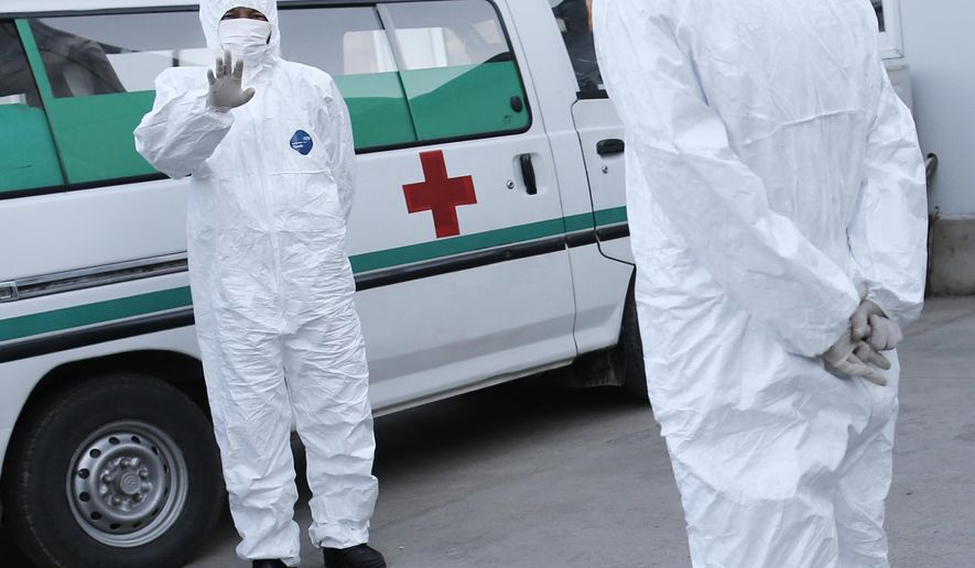 FILE - In this Oct. 27, 2014 photo, medical personnel in protective suits stand by an ambulance at the Sunan International Airport in Pyongyang, North Korea. North Korea, never a country to take the threat of foreign invasion lightly, has been under virtual lockdown since October to keep the Ebola virus from crossing its borders. But two leading travel agencies that specialize in the small but growing North Korea market say they have confirmed the North may be ready to open up its doors again soon. (AP Photo/Wong Maye-E, File)