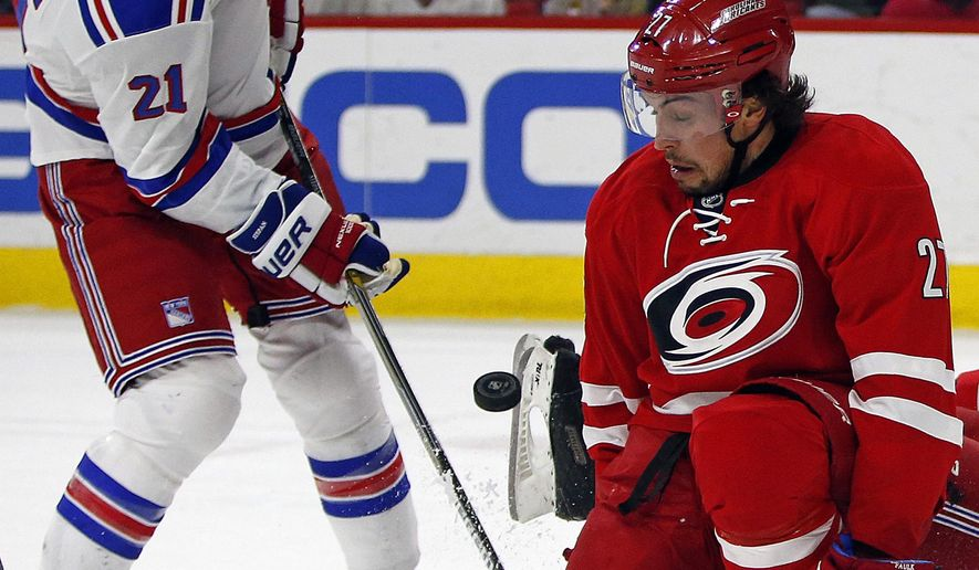 New York Rangers' Derek Stepan (21) battles Carolina Hurricanes' Justin Faulk (27) for the puck in front of the net during the first period of an NHL hockey game in Raleigh, N.C., Saturday, Dec. 20, 2014. (AP Photo/Karl B DeBlaker)