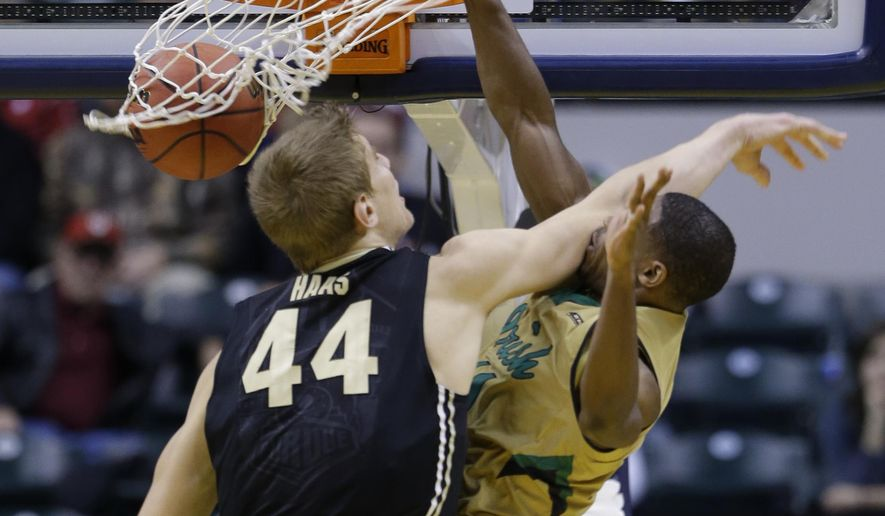 Notre Dame guard Demetrius Jackson (11), right, is hit by Purdue center Isaac Haas (44) while dunking in the second half of an NCAA college basketball game in Indianapolis, Saturday, Dec. 20, 2014. Notre Dame defeated Purdue 94-63. (AP Photo/Michael Conroy)