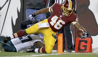 Washington Redskins running back Alfred Morris (46) dives into the end zone for a touchdown under pressure from Philadelphia Eagles free safety Malcolm Jenkins (27) during the first half of an NFL football game in Landover, Md., Saturday, Dec. 20, 2014. (AP Photo/Alex Brandon)