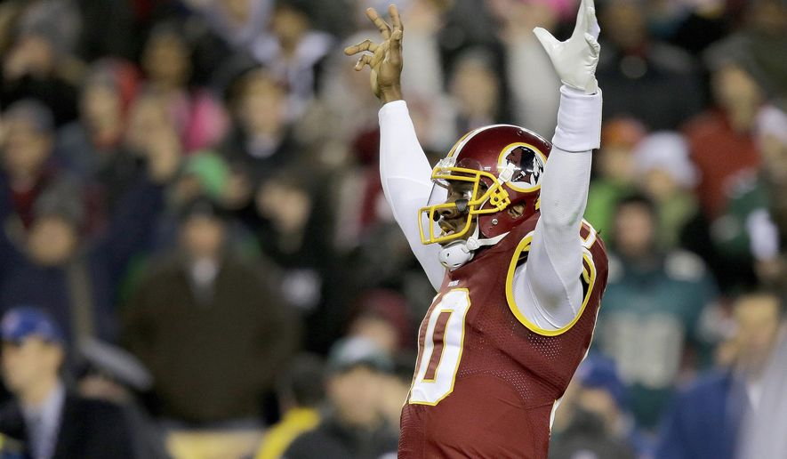 Washington Redskins quarterback Robert Griffin III celebrates running back Alfred Morris's touchdown during the first half of an NFL football game against the Philadelphia Eagles in Landover, Md., Saturday, Dec. 20, 2014. (AP Photo/Mark Tenally)