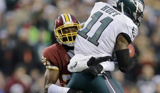 Washington Redskins cornerback Bashaud Breeland (26) picks up Philadelphia Eagles wide receiver Josh Huff (11) during the first half of an NFL football game in Landover, Md., Saturday, Dec. 20, 2014. (AP Photo/Patrick Semansky)
