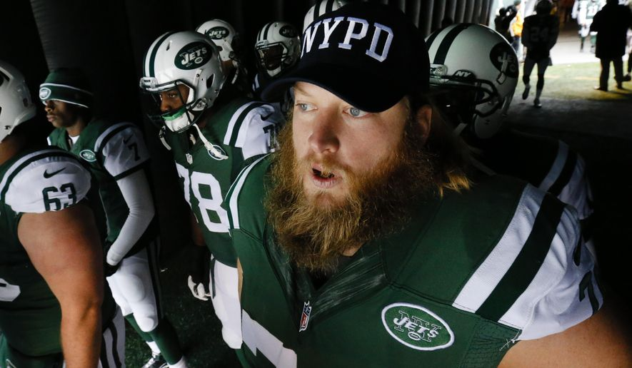 New York Jets center Nick Mangold (74) wears an NYPD hat as he waits to go on the field for the start of an NFL football game against the New England Patriots, Sunday, Dec. 21, 2014, in East Rutherford, N.J. (AP Photo/Julio Cortez)