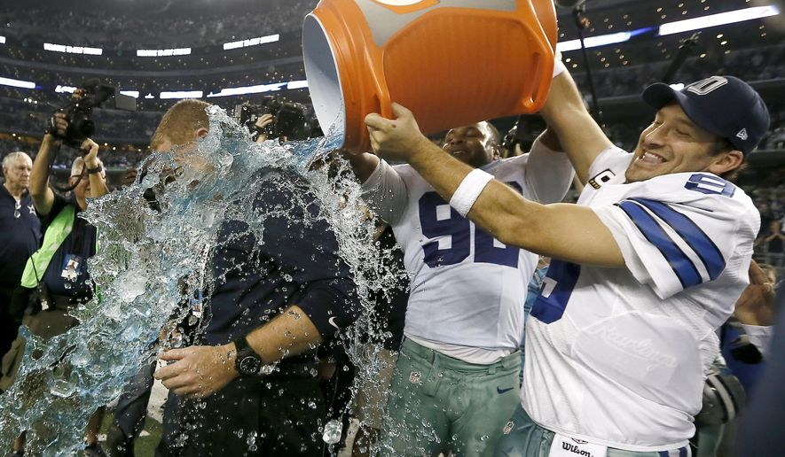 Dallas Cowboys head coach Jason Garrett is doused by Dallas Cowboys' Jeremy Mincey, center and quarterback Tony Romo, right, after their 42-7 win over the Indianapolis Colts in an NFL football game, Sunday, Dec. 21, 2014, in Arlington, Texas. The Cowboys won 42-7. (AP Photo/Brandon Wade)