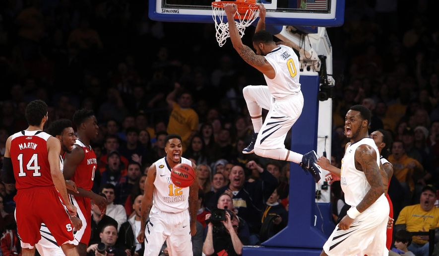 West Virginia's Tarik Phillip (12) and Elijah Macon, right, celebrate as teammate Jaysean Paige (0) dunks against North Carolina State during the first half of an NCAA college basketball game Saturday, Dec. 20, 2014, in New York. (AP Photo/Jason DeCrow)