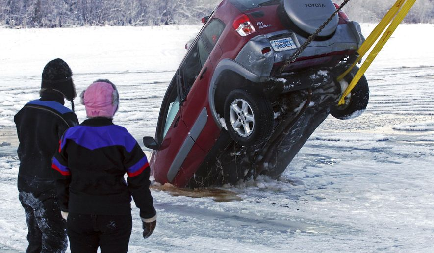 In this Dec. 19, 2014 photo, a dive crew watches the recovery of a vehicle from the icy water near the Pike's Landing Chena River Ice Bridge entrance in Fairbanks, Alaska. At least two vehicles recently sank into the Chena River on a section long used as an ice-covered shortcut between Airport Way and Chena Small Tracts Road. (AP Photo/The Fairbanks Daily News-Miner, Eric Engman)