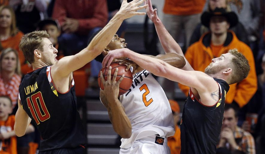 Oklahoma State guard Le'Bryan Nash (2) is double-teamed by Maryland guard Jake Layman (10) and forward Evan Smotrycz, right, in the second half of an NCAA college basketball game in Stillwater, Okla., Sunday, Dec. 21, 2014. Maryland won 73-64. (AP Photo/Sue Ogrocki)