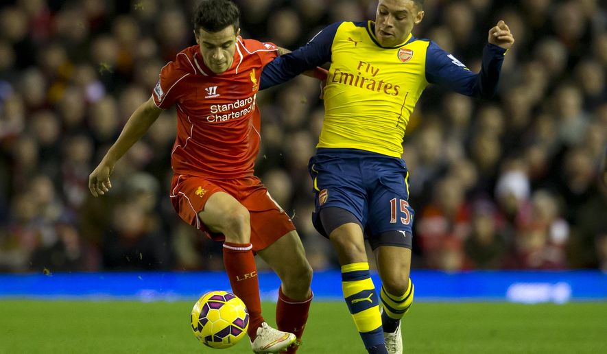 Liverpool's  Philippe Coutinho, left, fights for the ball against Arsenal's Alex Oxlade-Chamberlain during the English Premier League soccer match between Liverpool and Arsenal at Anfield Stadium, Liverpool, England, Sunday Dec. 21, 2014. (AP Photo/Jon Super)