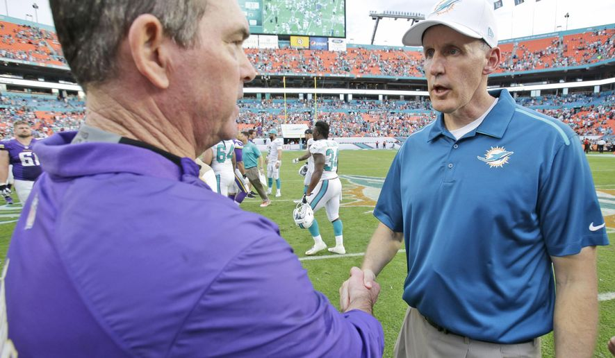 Minnesota Vikings head coach Mike Zimmer, left, and Miami Dolphins head coach Joe Philbin shake hands after the Dolphins defeated the Vikings 37-35 in an NFL football game, Sunday, Dec. 21, 2014 in Miami Gardens, Fla. (AP Photo/Wilfredo Lee)