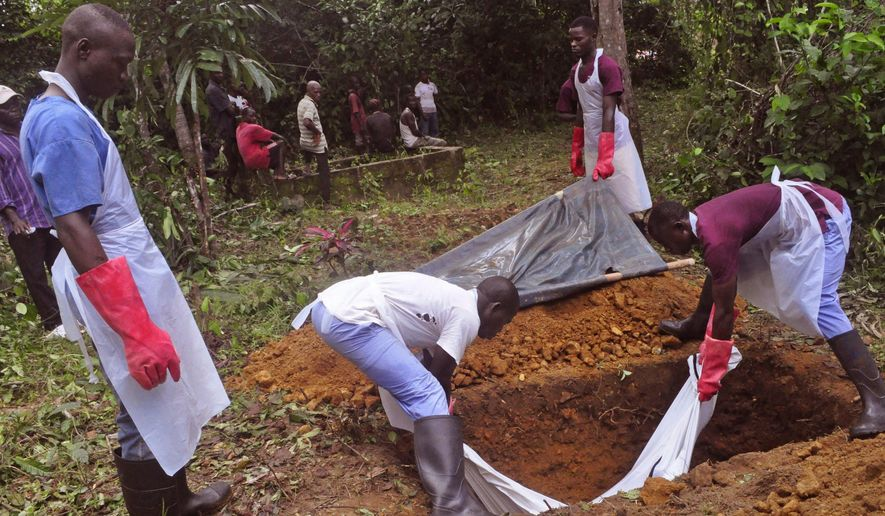 FILE- In this Saturday Nov. 8, 2014 file photo, Ebola health care workers bury the body of a person suspected of dying of Ebola virus on the outskirts of Monrovia Liberia. Ebola has killed more than 2,000 people in Sierra Leone and unsafe burials may be responsible for up to 70 percent of new infections, say experts. Officials are resorting to increasingly desperate measures to clamp down on traditional burials in Sierra Leone, where Ebola is now spreading fastest. The head of the Ebola response has even threatened to jail people who prepare the corpses of their loved ones.  (AP Photo/Abbas Dulleh, File)