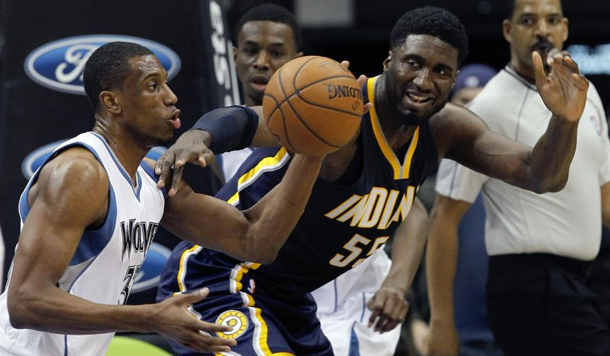 Minnesota Timberwolves forward Thaddeus Young, left, and Indiana Pacers center Roy Hibbert, right, reach for a loose ball during the first quarter of an NBA basketball game in Minneapolis, Sunday, Dec. 21, 2014. (AP Photo/Ann Heisenfelt)