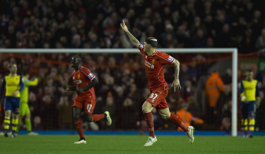 Liverpool's Martin Skrtel, centre right, celebrates after scoring a late goal against Arsenal during the English Premier League soccer match between Liverpool and Arsenal at Anfield Stadium, Liverpool, England, Sunday Dec. 21, 2014. (AP Photo/Jon Super)